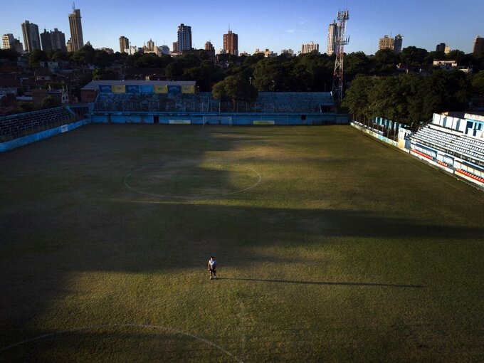 Striker Nicolas Caballero of the second division Resistencia football club stands on his team's pitch before a training session, in Asuncion, Paraguay, Tuesday, Feb. 2, 2021. Caballero, 32, who hasn't been paid by his club for more than a year, now has a food stall that sells barbecue on the streets of Asuncion to survive during the COVID-19 pandemic. (AP Photo/Jorge Saenz)