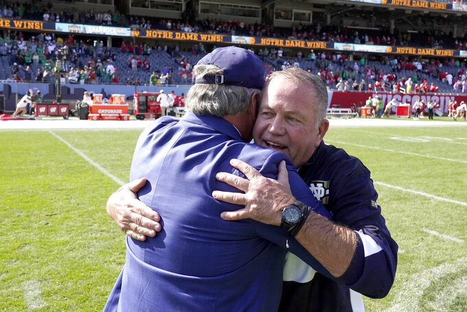 Notre Dame head coach Brian Kelly, right, is hugged by Athletic Director Jack Swarbrick Jr.,after the team's 41-13 win over Wisconsin after an NCAA college football game Saturday, Sept. 25, 2021, in Chicago. (AP Photo/Charles Rex Arbogast)