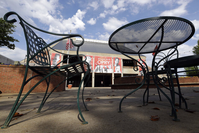 In this April 28, 2020, photo, empty tables and chairs sit in the plaza outside the Grand Ole Opry House in Nashville, Tenn. The Opry has suspended all events through May 16 due to the coronavirus pandemic. As businesses start to gradually reopen across the state, Tennessee tourism destinations like the Grand Ole Opry, Graceland and Dollywood remain closed Wednesday. But many of them are preparing to start welcoming visitors once again in a state where tourists spent $22 billion in 2018. (AP Photo/Mark Humphrey)