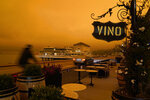 FILE - In this Sept. 9, 2020, file photo, a bicyclist rides past a seating area outside a wine bar as smoke from wildfires darken the morning sky in Sausalito, Calif. Smoke from the West Coast wildfires has tainted grapes in some of the nation's most celebrated wine regions. The resulting ashy flavor could spell disaster for the 2020 vintage. (AP Photo/Eric Risberg, File)
