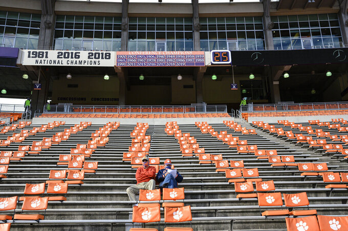FILE - In this Oct. 31, 2020, file photo, Clemson fans arrive early before an NCAA college football game against Boston College in Clemson, S.C. Clemson, which has played in four of the past six national title games, estimated a university-wide loss of between $70 million and $135 million due to COVID-19 in the last fiscal year. About a third came from lost athletics revenue, and the vast majority of that came from reduced football ticket sales to ensure proper social distancing. ( Josh Morgan/Pool Photo via AP, File)