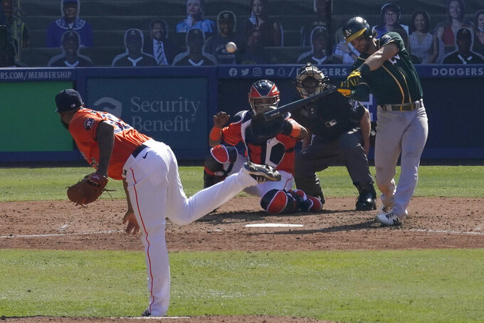 Oakland Athletics' Chad Pinder, right, hits a three-run home run off of Houston Astros pitcher Josh James, left, during the seventh inning of Game 3 of a baseball American League Division Series in Los Angeles, Wednesday, Oct. 7, 2020. (AP Photo/Marcio Jose Sanchez)