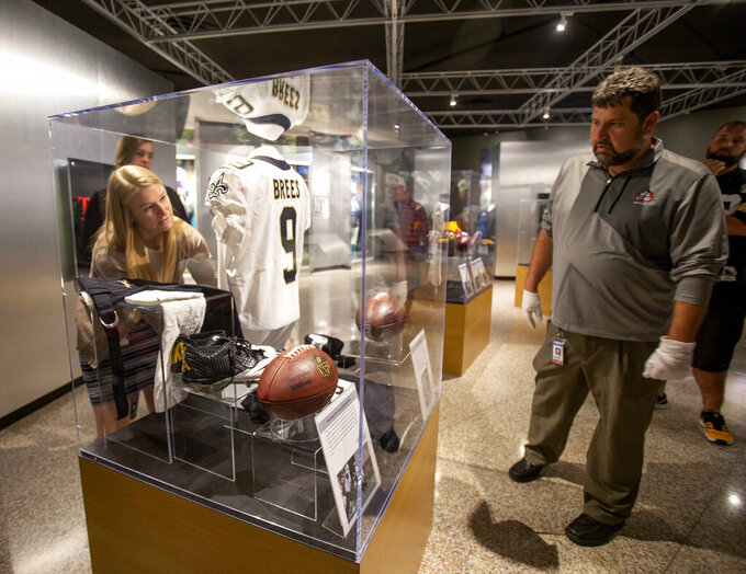 FILE - In this Oct. 9, 2018, file photo, Pro Football Hall of Fame curator Jason Aikens, right, watches Rachel Knapp as they work on a display in Canton, Ohio, of memorabilia of New Orleans Saints quarterback Drew Brees from his record-setting game against the Washington Redskins. Since opening in 1963 in Canton, Ohio, the hall just keeps growing, with a now 135,000-square foot building still not enough space to display all the jerseys, helmets, balls, gloves, Super Bowl rings and, of course, Hall of Fame busts. (Bob Rossiter/The Canton Repository via AP, File)