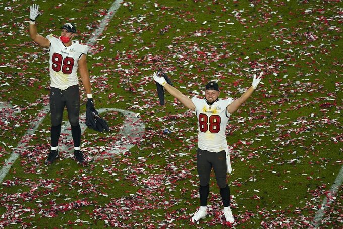 Tampa Bay Buccaneers' Anthony Nelson (98) and tight end Tanner Hudson (88) celebrate on the field at the end of the NFL Super Bowl 55 football game against the Kansas City Chiefs, Sunday, Feb. 7, 2021, in Tampa, Fla. The Buccaneers defeated the Chiefs 31-9 to win the Super Bowl. (AP Photo/Charlie Riedel)