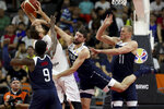 Serbia's Nikola Milutinov keeps the ball away from United States' Jaylen Brown, left, United States' Joe Harris, center and United States' Mason Plumlee at right during a consolation playoff game for the FIBA Basketball World Cup in Dongguan in southern China's Guangdong province on Thursday, Sept. 12, 2019. The U.S. will leave the World Cup with its worst finish ever in a major international tournament, assured of finishing no better than seventh after falling to Serbia 94-89 in a consolation playoff game on Thursday night. (AP Photo/Ng Han Guan)