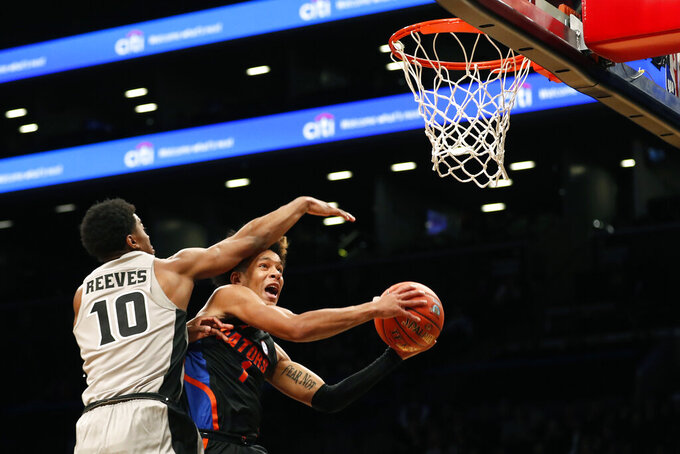 Florida guard Tre Mann (1) drives against Providence Friars guard A.J. Reeves (10) during the first half of an NCAA college basketball game at Barclays Center, Tuesday, Dec. 17, 2019, in New York. (AP Photo/Michael Owens)