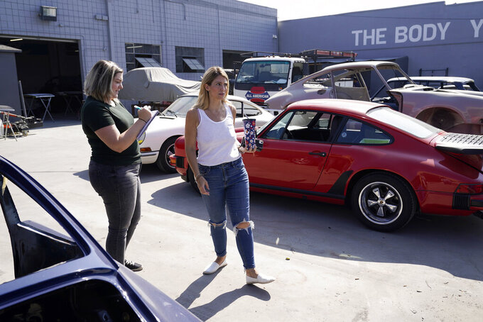 Laurina Esposito, right, co-owner of Espo Restoration, which specializes in restoring Porsches, makes the rounds with executive assistant Loretta Miller at her shop Monday, Oct. 19, 2020, in the North Hollywood section of Los Angeles. Esposito and her business partner were diagnosed with coronavirus in early September. She was very ill for three weeks and did as much work as she could on her laptop in bed, but at times was too exhausted. (AP Photo/Marcio Jose Sanchez)