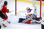 A shot by Canada's Marie-Philip Poulin, left, hits the post as U.S. goalie Nicole Hensley looks back during the third period of the IIHF hockey women's world championships title game in Calgary, Alberta, Tuesday, Aug. 31, 2021. (Jeff McIntosh/The Canadian Press via AP)
