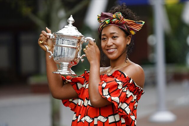Naomi Osaka, of Japan, holds up the championship trophy while posing for photographs at the Billie Jean King National Tennis Center Sunday, Sept. 13, 2020, in New York.(AP Photo/Frank Franklin II)