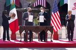 FILE - In this June 8, 2021 file photo, John Creamer, Chargé d'Affaires U.S. Embassy, left center, and Mexico's Foreign Minister Marcelo Ebrard, hold up signed documents as Vice President Kamala Harris, left, and Mexican President Andres Manuel Lopez Obrador, applaud at a signing ceremony at the National Palace in Mexico City. A gathering of leaders from Latin America and the Caribbean in Mexico City on Saturday, Sept. 17, 2021,  s the latest sign of Mexico flexing its diplomatic muscle as it looks to assert itself as the new mediator between the region and the United States. (AP Photo/Jacquelyn Martin, File)