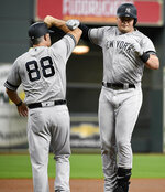 New York Yankees' Luke Voit, right, celebrates his solo home run off Houston Astros starting pitcher Gerrit Cole with third base coach Phil Nevin during the first inning of a baseball game, Tuesday, April 9, 2019, in Houston. (AP Photo/Eric Christian Smith)