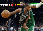 Milwaukee Bucks forward Khris Middleton (22) drives past Boston Celtics guard Kyrie Irving in the second quarter of an NBA basketball game, Friday, Dec. 21, 2018, in Boston. (AP Photo/Elise Amendola)
