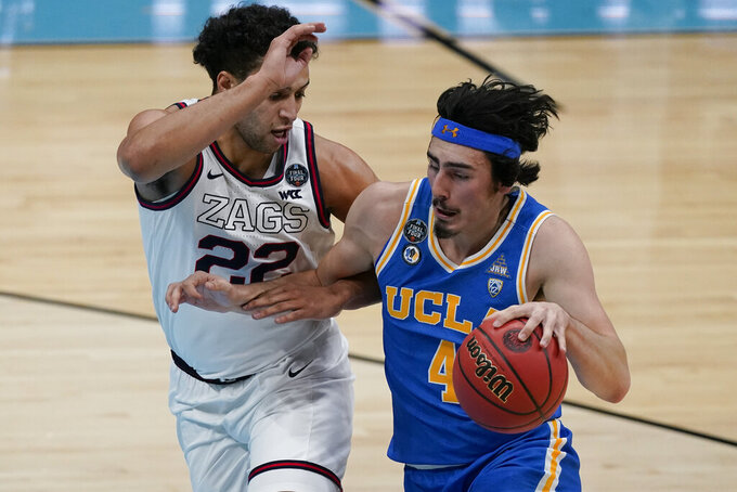 UCLA guard Jaime Jaquez Jr. (4) drives up court past Gonzaga forward Anton Watson (22) during the first half of a men's Final Four NCAA college basketball tournament semifinal game, Saturday, April 3, 2021, at Lucas Oil Stadium in Indianapolis. (AP Photo/Michael Conroy)