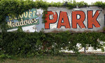 ADVANCE ON THURSDAY, SEPT. 12 FOR USE ANY TIME AFTER 3:01 A.M. SUNDAY SEPT 15 - A faded sign at the Denver Meadows Mobile Home and RV Park stands in Aurora, Colo., on Friday, Aug. 30, 2019. Residents, most of whom have been displaced, tried to buy the park but were unsuccessful. Most of the homes are now abandoned and are slated for demolition as the park closes for possible redevelopment. (AP Photo/Thomas Peipert)