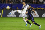 LA Galaxy midfielder Uriel Antuna, left, shoots next to Montreal Impact defender Daniel Lovitz during the second half of an MLS soccer match in Carson, Calif., Saturday, Sept. 21, 2019. (AP Photo/Chris Carlson)