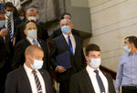Israeli Prime Minister Benjamin Netanyahu, third right, wears a protective face mask, as he makes his way to attend the swearing in ceremony of his new government, at the Knesset, Israel's parliament, in Jerusalem, Sunday, May 17, 2020. Netanyahu is finally swearing in his new government after three deadlocked and divisive elections, a year and a half of political paralysis and another three-day delay because of political infighting in his Likud party over coveted Cabinet posts. (Alex Kolomiensky/Yedioth Ahronoth/Pool via AP)