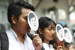 Human rights activists for Amnesty International hold masks of Thai pro-democracy leader Sirawith Seritiwat during a protest at police headquarter in Bangkok, Thailand, Wednesday, July 3, 2019. Rights groups are urging Thai authorities to investigate attacks against pro-democracy activists after one was beaten and left unconscious on a sidewalk last week. (AP Photo/Sakchai Lalit)