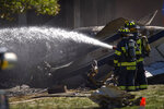 Firefighters work near the wreckage of a Cessna Citation 560X aircraft that crashed into a building at the manufacturing company Trumpf Inc. in Farmington, Conn., and caught fire Thursday, Sept. 2, 2021, after taking off from nearby Robertson Airport in Plainville, Conn. The small jet crashed shortly after taking off, killing all four people aboard, officials said. (Mark Mirko/Hartford Courant via AP)