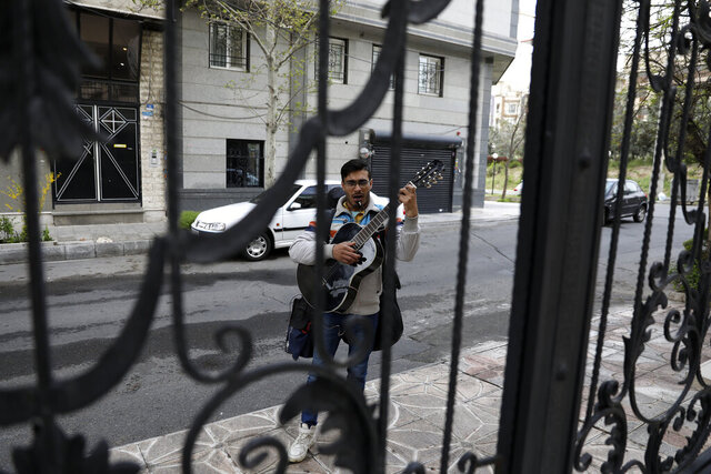A street musician sings and plays music on an empty lane in Tehran, Iran, Thursday, March 26, 2020. Iran is battling the worst new coronavirus outbreak in the region and authorities have advised people to stay at home and trying to enforce new policy imposing the kinds of lockdowns when the country spending the new year holidays. (AP Photo/Vahid Salemi)