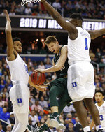 Michigan State guard Matt McQuaid (20) is stopped under the basket by Duke forwards Zion Williamson (1) and Javin DeLaurier (12) during the first half of an NCAA men's East Regional final college basketball game in Washington, Sunday, March 31, 2019. (AP Photo/Alex Brandon)