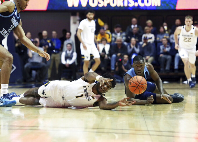 West Virginia Derek Culver (1) reaches for the ball as he is defended by Rhode Island forward Cyril Langevine, behind, during the second half of an NCAA college basketball game Sunday, Dec. 1, 2019, in Morgantown, W.Va. (AP Photo/Kathleen Batten)