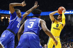 Marquette's Markus Howard (0) shoots against Xavier's Naji Marshall (13) and Quentin Goodin (3) in the second half of an NCAA college basketball game, Saturday, Jan. 26, 2019, in Cincinnati. (AP Photo/John Minchillo)