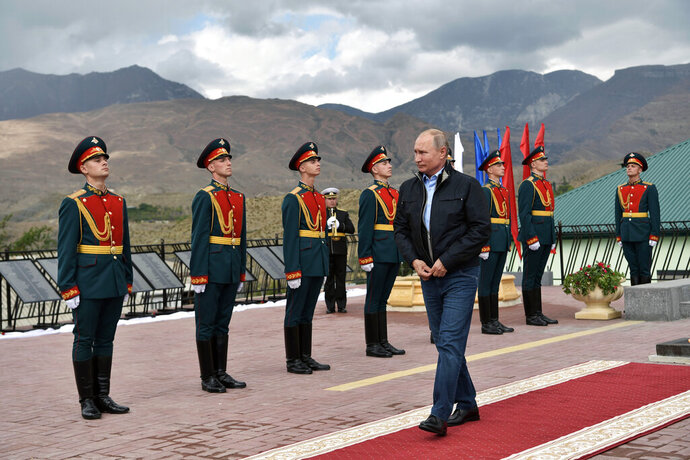 Russian President Vladimir Putin, center, walks past honor guards after laying flowers at the monument to the soldiers and militiaman of WWII and local conflicts in the Botlikh village, Dagestan, Russia, Thursday, Sept. 12, 2019. (Alexei Nikolsky, Sputnik, Kremlin Pool Photo via AP)