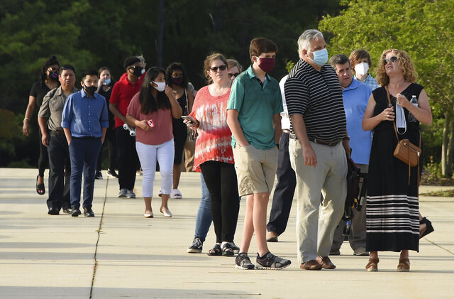In this Wednesday, May 20, 2020 photo, friends and family members attend Spain Park High School's graduation ceremony at the Hoover Met, in Hoover, Ala. Everyone attending the ceremony had to wear a mask as a precaution against the spread of the coronavirus. (Joe Songer/The Birmingham News via AP)