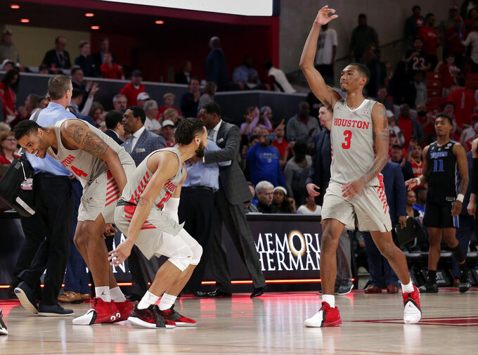 Houston forward Breaon Brady, left, guard Galen Robinson Jr., middle, and guard Armoni Brooks (3) celebrate their 90-77 win against Memphis after the second half of an NCAA college basketball game Sunday, Jan. 6, 2019, in Houston. (AP Photo/Michael Wyke)