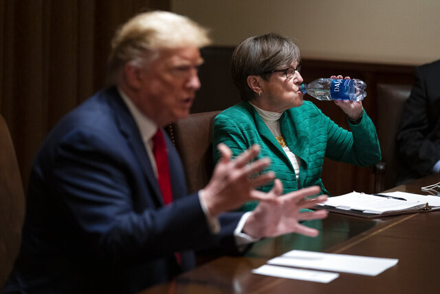 Kansas Gov. Laura Kelly listens as President Donald Trump speaks during a meeting in the Cabinet Room of the White House, Wednesday, May 20, 2020, in Washington. (AP Photo/Evan Vucci)