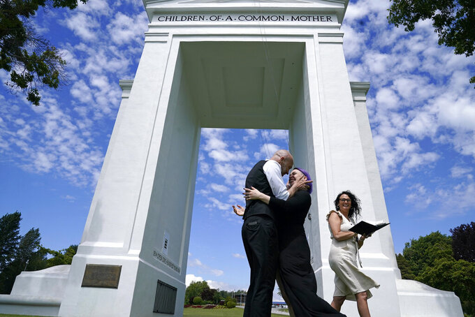 Joel Gardiner, left, embraces his new bride Mandi Gardiner as officiant Brooke Bakogeorge steps away after marrying the couple at the arch separating the U.S. from Canada at Peace Arch Historical State Park Tuesday, June 8, 2021, in Blaine, Wash. Gardiner, of Canada, walked across the border at the park into the U.S. earlier in the day to wed his American sweetheart. The border has been closed to nonessential travel since March 2020, but Canadians have been allowed to walk over a ditch into the U.S. park and weddings have become routine there. (AP Photo/Elaine Thompson)