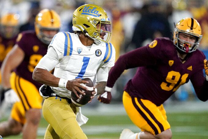 UCLA quarterback Dorian Thompson-Robinson (1) scrambles as Arizona State defensive end Michael Matus (91) pursues during the first half of an NCAA college football game Saturday, Dec. 5, 2020, in Tempe, Ariz. (AP Photo/Matt York)