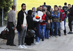 Syrian refugees line up as they wait to board a bus to take them home to Syria, in Beirut, Lebanon, Tuesday, Dec. 3, 2019. Hundreds of Syrian refugees have headed home in the first batch to leave Lebanon since protests broke out more than a month ago. Lebanon is hosting some 1 million Syrian refugees who fled their country after the war broke out eight years ago. (AP Photo/Hussein Malla)