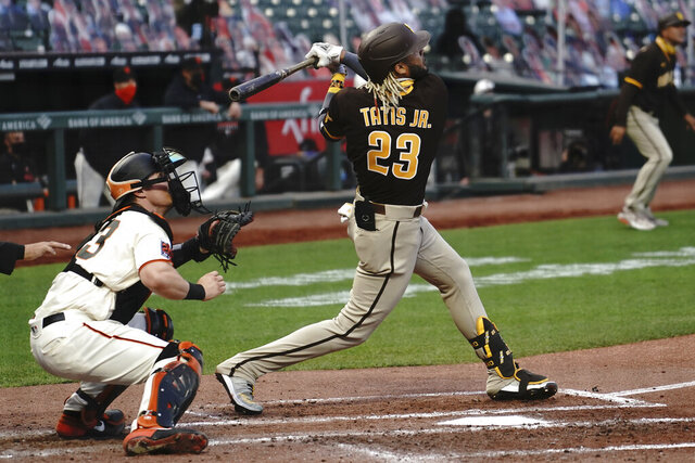 San Diego Padres' Fernando Tatis Jr. (23) hits a three-run home run in front of San Francisco Giants catcher Tyler Heineman during the third inning of a baseball game in San Francisco, Tuesday, July 28, 2020. (AP Photo/Jeff Chiu)