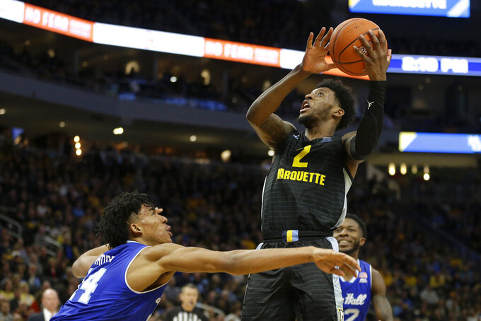Marquette's Sacar Anim (2) shoots over Seton Hall's Jared Rhoden during the first half of an NCAA college basketball game Saturday, Feb. 29, 2020, in Milwaukee. (AP Photo/Aaron Gash)
