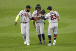 Atlanta Braves' Marcell Ozuna, left, Ronald Acuna Jr., center, and Adam Duvall (23) celebrate after a baseball game against the Washington Nationals, Saturday, Sept. 12, 2020, in Washington.  (AP Photo/Nick Wass)