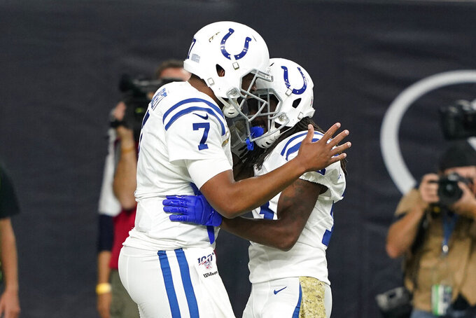 Indianapolis Colts quarterback Jacoby Brissett (7) celebrates with teammate T.Y. Hilton (13) after a touchdown against the Houston Texans during the first half of an NFL football game Thursday, Nov. 21, 2019, in Houston. (AP Photo/David J. Phillip)