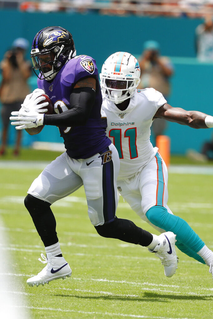 Baltimore Ravens free safety Earl Thomas (29) intercepts a pass, as Miami Dolphins wide receiver DeVante Parker (11), attempts to tackle, during the first half at an NFL football game, Sunday, Sept. 8, 2019, in Miami Gardens, Fla. (AP Photo/Wilfredo Lee)