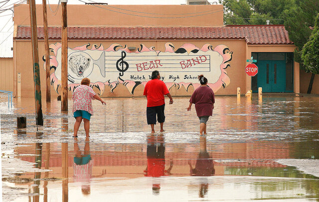 FILE - In this Aug. 16, 2006, file photo, Hatch, N.M., residents walk through floodwaters in their town. A plan to spend $100 million to fix dams throughout New Mexico - a state with the highest percentage of high-hazard dams in the country, passed its first test Tuesday, Feb. 11, 2020, amid an urgent call to upgrade the facilities over worries about the loss of life. (AP Photo/David Pierre, File)