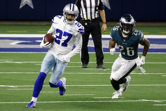 Dallas Cowboys cornerback Trevon Diggs (27) intercepts a pass thrown by Philadelphia Eagles quarterback Jalen Hurts as running back Miles Sanders (26) gives chase in the second half of an NFL football game in Arlington, Texas, Sunday, Dec. 27. 2020. (AP Photo/Michael Ainsworth)