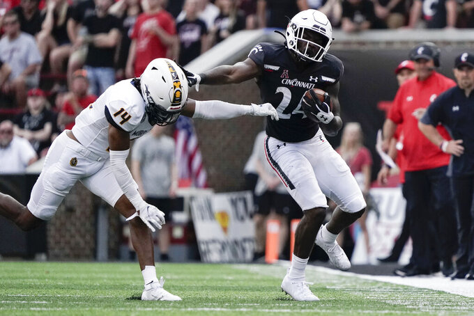 Cincinnati running back Jerome Ford (24) is pushed out of bounds by Murray State cornerback Cayvian Holmes (14) during the second half of an NCAA college football game Saturday, Sept. 11, 2021, in Cincinnati. (AP Photo/Jeff Dean)