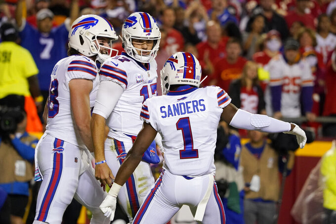 Buffalo Bills quarterback Josh Allen, center, is congratulated by Dawson Knox, left, and Emmanuel Sanders (1) after scoring during the first half of an NFL football game against the Kansas City Chiefs Sunday, Oct. 10, 2021, in Kansas City, Mo. (AP Photo/Ed Zurga)