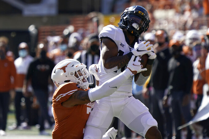 West Virginia's Winston Wright Jr., right, catches a pass against Texas' Caden Sterns, left, during the first half of an NCAA college football game in Austin, Texas, Saturday, Nov. 7, 2020. (AP Photo/Chuck Burton)