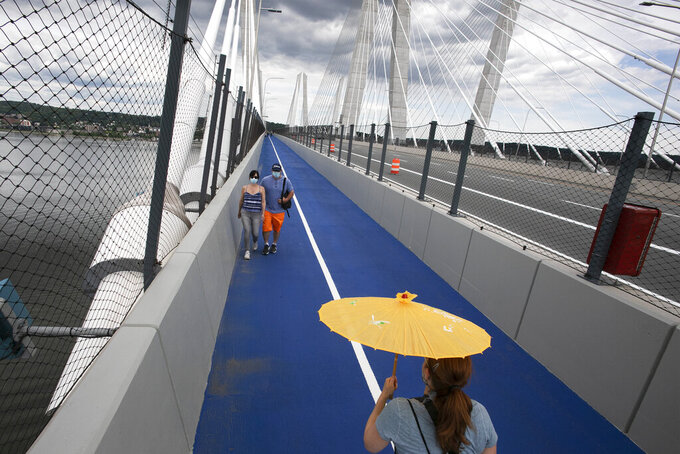 A woman carries a parasol as she walks on the Gov. Mario M. Cuomo Bridge bike and pedestrian path on its opening day, Monday, June 15, 2020 in Tarrytown, N.Y. The new 3.6 mile path runs from Tarrytown across the Hudson River to South Nyack, N.Y. (AP Photo/Mark Lennihan)