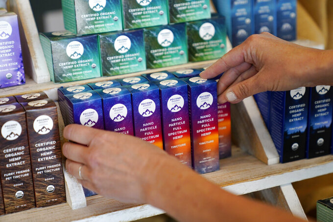 Ashley Walsh, founder of Pocono Organics farm, arranges CBD products for sale at the farm adjacent to Pocono Raceway, Friday, June 25, 2021, in Long Pond, Pa. The 380 acre farm is the title sponsor for Saturday's NASCAR auto race, The Pocono Organics CBD 325, the first Cup race with a CBD sponsorship. (AP Photo/Matt Slocum)