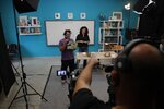 A cameraman gives directions to teacher Rania Koukli as she prepares to record lessons that are broadcast on public television, at an elementary school in Athens, Wednesday, Nov. 18, 2020. Most other European countries have vowed to keep schools open, but the pandemic has hit Greece hard for the first time in recent weeks following a successful lockdown in the spring, overwhelming hospitals in parts of the country. State television is making and broadcasting lessons, while teachers sit in empty classrooms talking to remote students. Despite some problems, they say it keeps children in touch with their schools. (AP Photo/Thanassis Stavrakis)