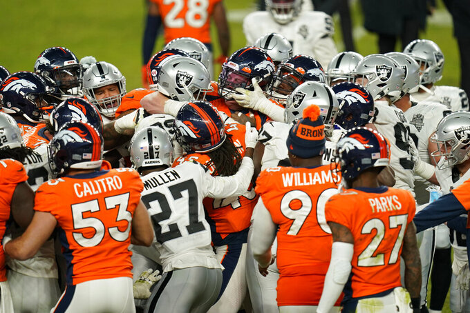 Las Vegas Raiders and Denver Broncos players get in a scrum after an NFL football game, Sunday, Jan. 3, 2021, in Denver. (AP Photo/Jack Dempsey)