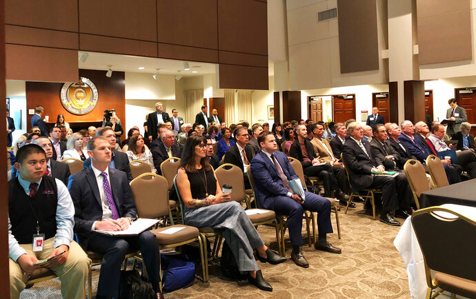 Prize winners and other observers look on Wednesday, Sept. 12, 2018, in Columbus, Ohio, as another $2.4 million is awarded through the Ohio Opioid Technology Challenge. Among winning ideas were a device to treat withdrawal symptoms in opioid-addicted infants and a glove that changes color when first responders come into contact with an opioid. (AP Photo/Julie Carr Smyth)