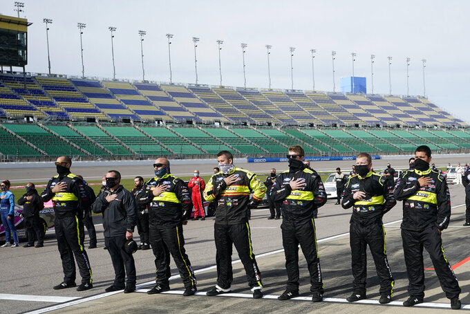 Teams stand for the national anthem before a NASCAR Truck Series auto race at Kansas Speedway in Kansas City, Kan., Saturday, Oct. 17, 2020. (AP Photo/Orlin Wagner)