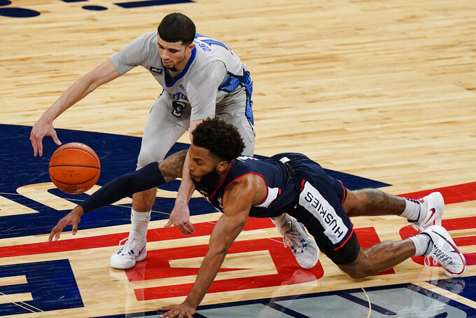 Connecticut's R.J. Cole, bottom, knocks the ball away from Creighton's Marcus Zegarowski during the first half of an NCAA college basketball game in the semifinals in the Big East men's tournament Friday, March 12, 2021, in New York. (AP Photo/Frank Franklin II)